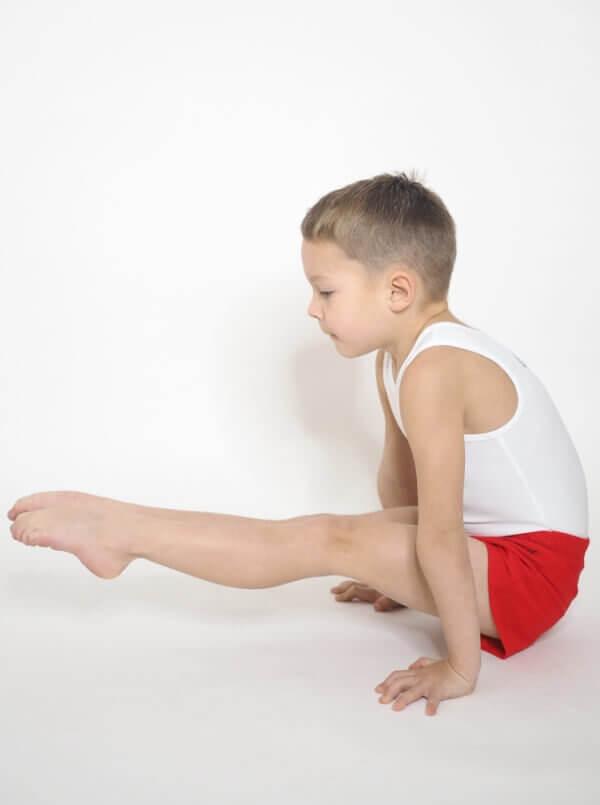 gymnasta v přednosu s červenýma trenkama a bílým dresem